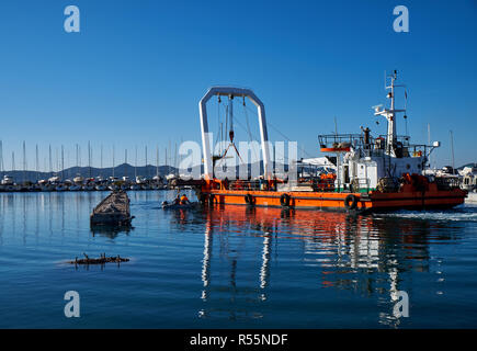 Zadar, Croatia, November 29, 2018.  Leverage crane on barge lifting part of concrete pier being demolished and replaced - Stock Image