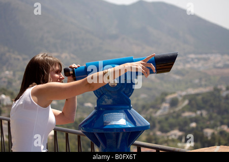 Young woman tourist looking though telescope pointing at a viewpoint in Mijas Pueblo, Costa del Sol, Andalucia, - Stock Image