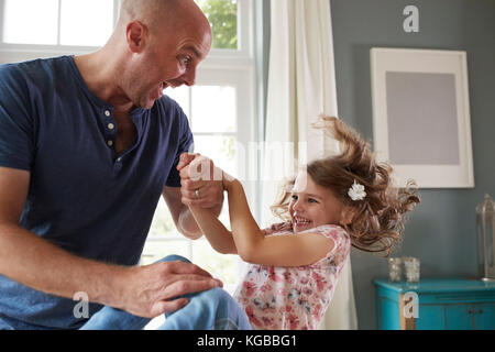 Father and daughter having fun jumping together at home - Stock Image