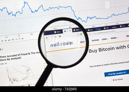 MONTREAL, CANADA - APRIL 26, 2019: Wallofcoins.com cryptocurrency digital assets exchange logo and home page on a laptop screen under magnifying glass - Stock Image