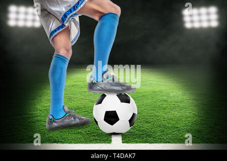 Spotlight on soccer player in action with football in brightly lit outdoor stadium. Focus on foreground and soccer ball with shallow depth of field on - Stock Image