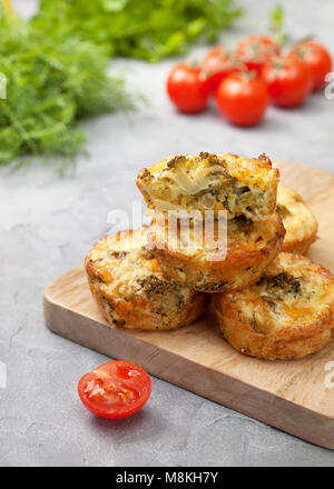 healthy breakfast. broccoli cheese bites (muffins), fresh tomatoes, fresh herbs on gray concrete background - Stock Image