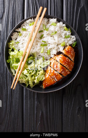 Japanese chicken teriyaki with rice and fresh salad close-up on a plate on the table. Vertical top view from above - Stock Image