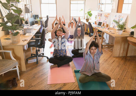 Creative business people practicing yoga in office - Stock Image