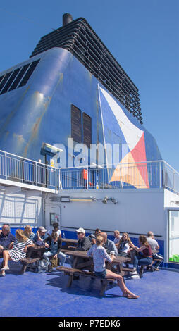 People sunning themselves on open rear deck of P&O Car Ferry leaving Dover with funnel in backgound. - Stock Image