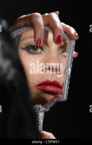 Girl Looking at Her Own Reflection in a Hand Mirror. - Stock Image