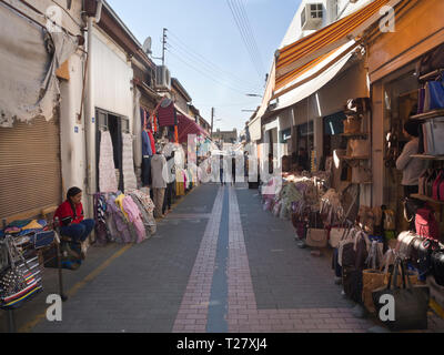 Market street on the Turkish part of the divided capital of Cyprus, Nicosia, clothes and bags are among the goods being offered - Stock Image