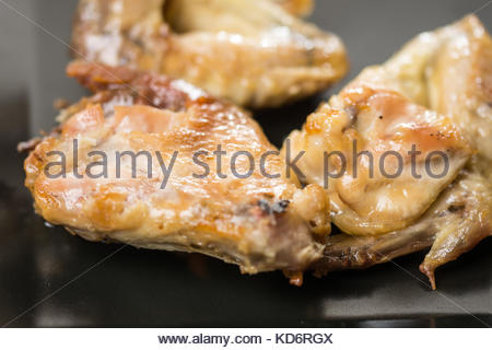 Fried chicken wings served on the black plate. - Stock Image