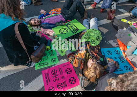 London, UK. 31st October 2018. People lock-on to block the roadway in front of Parliament after making the 'Declaration of Rebellion' against the British Government for its criminal inaction in the face of climate change catastrophe and ecological collapse. They listened to speeches by George Monbiot and Green Party MP Caroline Lucas and there were songs and poems. A number of activists brought large wreaths and lay down with them, with several lock-ons. Police tried to clear the road, but the protesters ignored them, taking a show of hands to remain blocking the road for another half hour.  M - Stock Image