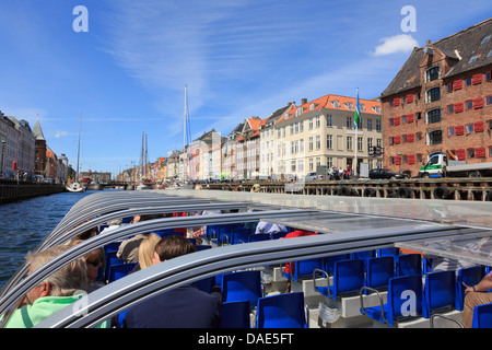 Tourists sightseeing on a canal tour boat in Nyhavn harbour, Copenhagen, Zealand, Denmark, Scandinavia - Stock Image
