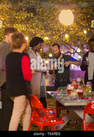 Friends celebrating with champagne at dinner garden party - Stock Image