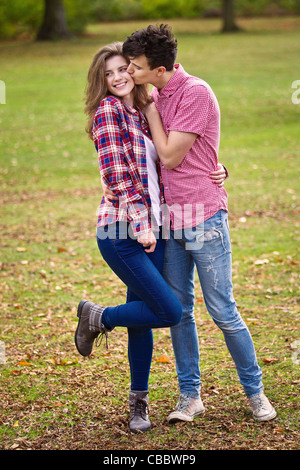Teenage couple kissing in park - Stock Image