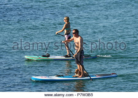 Worthing, UK. Sunday 8th July 2018. A pair of paddleboarders at sea on a very warm morning in Worthing, on the South Coast. Credit: Geoff Smith / Alamy Live News. - Stock Image