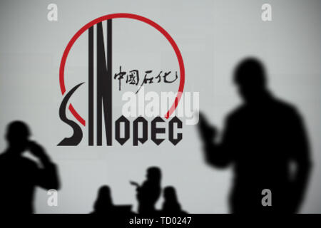 The Sinopec logo is seen on an LED screen in the background while a silhouetted person uses a smartphone in the foreground (Editorial use only) - Stock Image