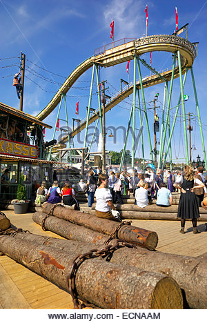Visitors to Oktoberfest in Munich, Germany, queue up to go on roller coaster ride. - Stock Image