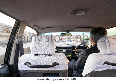 View from back seat of male taxi driver driving taxi, Higashiyama-ku, Kyoto, Honshu, Japan - Stock Image