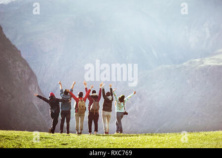 Happy hikers or friends stands against mountain valley with raised arms and having fun. Space for text - Stock Image