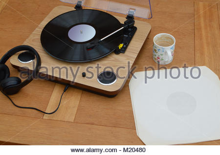 Classic record player with headphones and mug of coffee on wooden table. White empty record sleeve left on table. - Stock Image
