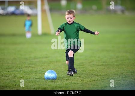 Young boy kicking soccer ball - Stock Image