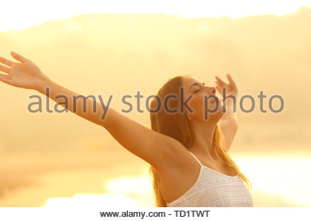Relaxed woman stretching arms breathing deep fresh air at sunset on the beach - Stock Image