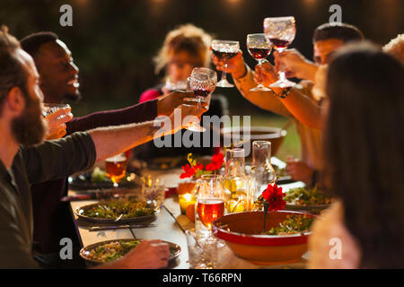 Friends toasting wine glasses at dinner garden party - Stock Image
