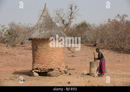Samba village, Yako Province, Burkina Faso; A woman pounding grain by her grain store. - Stock Image