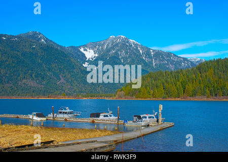 Boats tied up at dock with mountains in the background. - Stock Image