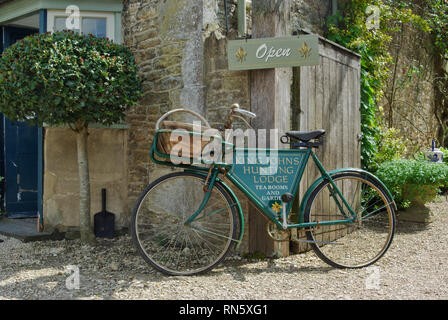 A sign, incorporated into an old bicycle, for King John's Hunting Lodge, tea rooms and restaurant in the historic village of Lacock, UK - Stock Image