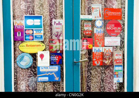 Restaurant doors in Montparnasse area of Paris, with guides and awards stickers. - Stock Image