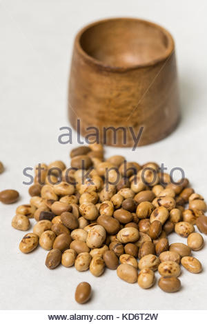 Soya beans with wooden pot on the white marble background. - Stock Image