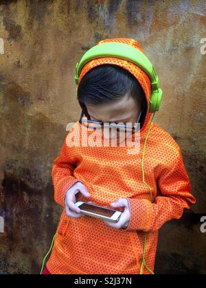 Young boy with black glasses listening to music on stereo headphones and playing with a phone. - Stock Image