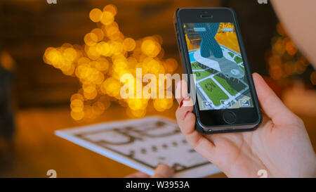 Woman using smartphone with augmented reality app and placing virtual model - Stock Image