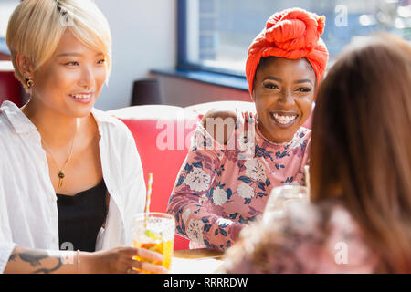 Happy young women friends drinking cocktails, talking in restaurant - Stock Image
