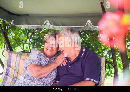 nice couple of beautiful caucasian senior 70 years old sit outdoor at home having fun with smiles and laugh. happy life together forever in love and e - Stock Image