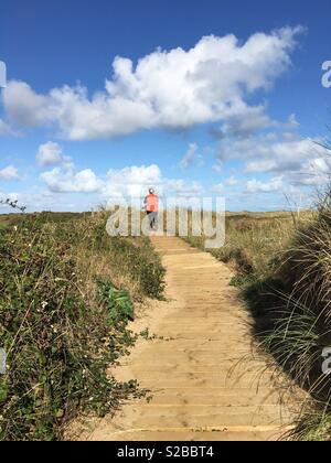 A young lady walks among a path across sand dunes. - Stock Image