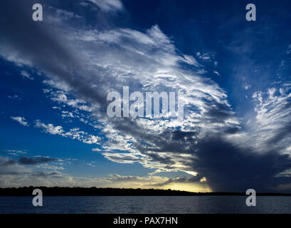 A spectacular inspirational brightly coloured atmospheric cloudy sky cloudscape featuring a Stratocumulus and Cirrus cloud formation in a mid blue sky - Stock Image