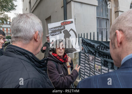 London, UK. 19th Dec, 2018. Maggie Zolobuaijluk of DPAC shows Liberal Democrats her banner with the names of around a hundred people killed by benefit cuts and sanctions at the protest in support of the parliamentary debate due later in the day on the cumulative impact of the cuts on the lives of disabled people. They say the government cuts and changes in benefits, along with inappropriate benefit sanctions, have had a disproportionate effect on disabled people, resulting in great hardship, denying people their rights and many deaths. Credit: Peter Marshall/Alamy Live News - Stock Image