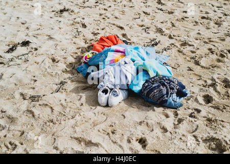 A pile of clothes left on the beach whilst people go swimming at Falmouth's Gyllngvase Beach 16-10-16 - Stock Image