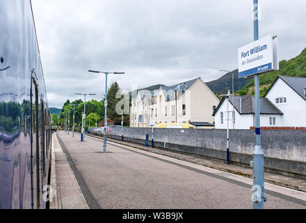 Fort William train station platform and name sign with ScotRail train on West Highland railway line, Scottish Highlands, Scotland, UK - Stock Image