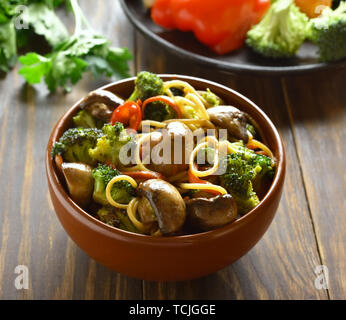 Egg noodles with vegetables in bowl on wooden table - Stock Image