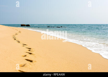 foot prints in a clear golden sand perfect beach next to a calm turquoise sea. - Stock Image