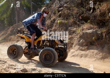 Adventure Tourism Quadrunner tourist on Four-wheel-drive Beach buggies on dirt road. - Stock Image