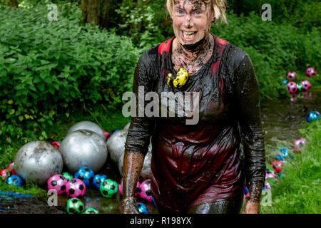 Mud covered women in a ditch - Stock Image