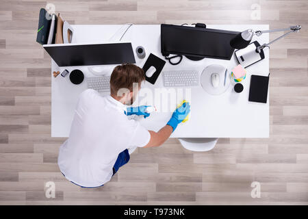 Janitor cleaning white desk in modern office - Stock Image