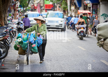 A woman carrying her bicycle in Hanoi, Vietnam, wearing a traditional conical hat. Women selling products on their bicycles are a common site in Hanoi - Stock Image