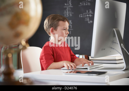 Young boy using computer in classroom - Stock Image