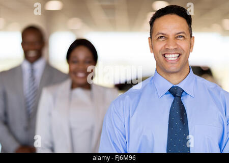 cheerful car dealership principal with staff on background - Stock Image