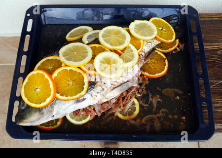 Prepared for  baking fish. Сarp filled with onions and walnutsand covered with slices of lemon and orange. Delicious homemade food. - Stock Image