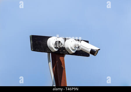 Security cctv cameras in front of blue sky - Stock Image