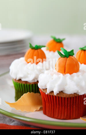 Pumpkin spice cupcakes with vanilla frosting decorated for Halloween and Thanksgiving - Stock Image